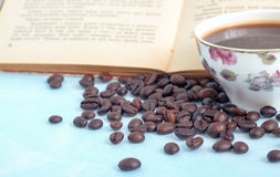 Roasted coffee beans in the background cup of hot coffee and open book Royalty Free Stock Photos