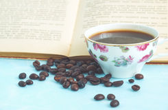 Roasted coffee beans in the background cup of hot coffee and open book Royalty Free Stock Images