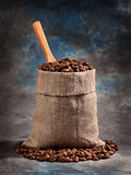 Roasted coffee beans in a bag with a scoop. On the beautiful background Stock Photos