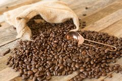 Roasted coffee beans in a bag on wooden background Royalty Free Stock Photos