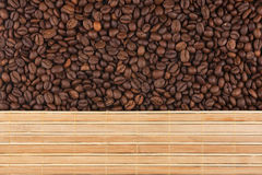 Roasted coffee beans and a bamboo mat Stock Photos