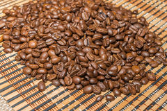 Roasted coffee beans on a bamboo mat. Sorting roasted coffee beans on a bamboo mat. Selective focus Royalty Free Stock Image