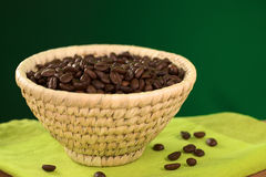 Roasted Coffee Beans in Basket. Roasted coffee beans in woven basket with green background (Selective Focus, Focus on the coffee beans in the middle of the Royalty Free Stock Photo
