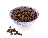 Roasted coffee beans in a bowl, some spilled beside. Dark roasted coffee beans in a blue and white ceramic bowl, some spilled beside, on a white background Stock Photography