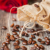Roasted coffee beans on a brown wooden background with coarse roughly woven burlap and red rose, grunge texture. Place Stock Photography