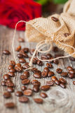 Roasted coffee beans on a brown wooden background, coarse roughly woven burlap and red rose, grunge texture. selective Stock Photo