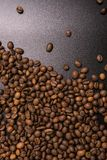 Roasted coffee beans in bulk on a black background. dark cofee roasted grain flavor aroma cafe, natural coffe shop background, top. View from above, copy space royalty free stock photography