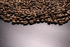 Roasted coffee beans in bulk on a black background. dark cofee roasted grain flavor aroma cafe, natural coffe shop background, top. View from above, copy space stock photos