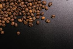 Roasted coffee beans in bulk on a black background. dark cofee roasted grain flavor aroma cafe, natural coffe shop background, top. View from above, copy space stock photo