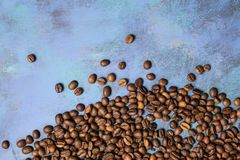 Roasted coffee beans in bulk on a blue background. dark cofee roasted grain flavor aroma cafe, natural coffe shop background, top. View from above, copy space stock photography