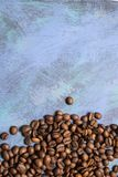 Roasted coffee beans in bulk on a blue background. dark cofee roasted grain flavor aroma cafe, natural coffe shop background, top. View from above, copy space royalty free stock photo