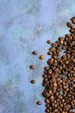 Roasted coffee beans in bulk on a blue background. dark cofee roasted grain flavor aroma cafe, natural coffe shop background, top. View from above, copy space royalty free stock photography