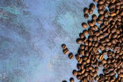 Roasted coffee beans in bulk on a blue background. dark cofee roasted grain flavor aroma cafe, natural coffe shop background, top. View from above, copy space stock images