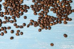 Roasted coffee beans in bulk on a blue wooden background. dark cofee roasted grain flavor aroma cafe, natural coffe shop. Background, top view from above, copy royalty free stock images