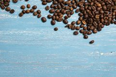 Roasted coffee beans in bulk on a blue wooden background. dark cofee roasted grain flavor aroma cafe, natural coffe shop. Background, top view from above, copy royalty free stock photos