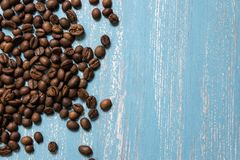 Roasted coffee beans in bulk on a blue wooden background. dark cofee roasted grain flavor aroma cafe, natural coffe shop. Background, top view from above, copy stock photography