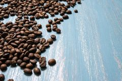 Roasted coffee beans in bulk on a blue wooden background. dark cofee roasted grain flavor aroma cafe, natural coffe shop. Background, top view from above, copy royalty free stock image