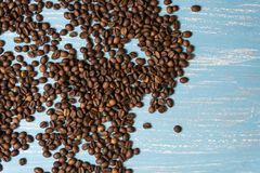Roasted coffee beans in bulk on a blue wooden background. dark cofee roasted grain flavor aroma cafe, natural coffe shop. Background, top view from above, copy royalty free stock photography