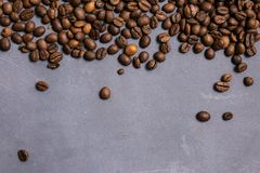 Roasted coffee beans in bulk on a gray concrete background. dark cofee roasted grain flavor aroma cafe, natural coffe shop. Background, top view from above stock images