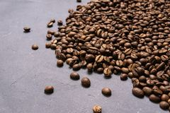 Roasted coffee beans in bulk on a gray concrete background. dark cofee roasted grain flavor aroma cafe, natural coffe shop. Background, top view from above stock photos