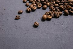 Roasted coffee beans in bulk on a gray concrete background. dark cofee roasted grain flavor aroma cafe, natural coffe shop. Background, top view from above royalty free stock photos