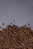 Roasted coffee beans in bulk on a gray concrete background. dark cofee roasted grain flavor aroma cafe, natural coffe shop. Background, top view from above royalty free stock photo
