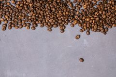 Roasted coffee beans in bulk on a gray concrete background. dark cofee roasted grain flavor aroma cafe, natural coffe shop. Background, top view from above royalty free stock photography