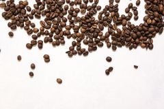 Roasted coffee beans in bulk on a light blue background. dark cofee roasted grain flavor aroma cafe, natural coffe shop background. Top view from above, copy stock image