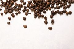 Roasted coffee beans in bulk on a light blue background. dark cofee roasted grain flavor aroma cafe, natural coffe shop background. Top view from above, copy royalty free stock photo