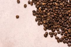 Roasted coffee beans in bulk on a light pink background. dark cofee roasted grain flavor aroma cafe, natural coffe shop background. Top view from above, copy stock image