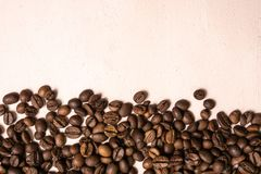 Roasted coffee beans in bulk on a light pink background. dark cofee roasted grain flavor aroma cafe, natural coffe shop background. Top view from above, copy stock photos