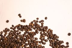 Roasted coffee beans in bulk on a light pink background. dark cofee roasted grain flavor aroma cafe, natural coffe shop background. Top view from above, copy royalty free stock photos