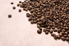Roasted coffee beans in bulk on a light pink background. dark cofee roasted grain flavor aroma cafe, natural coffe shop background. Top view from above, copy stock photo