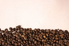 Roasted coffee beans in bulk on a light pink background. dark cofee roasted grain flavor aroma cafe, natural coffe shop background. Top view from above, copy royalty free stock image