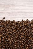 Roasted coffee beans in bulk on a light wooden background. dark cofee roasted grain flavor aroma cafe, natural coffe shop. Background, top view from above, copy royalty free stock photos