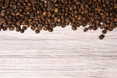 Roasted coffee beans in bulk on a light wooden background. dark cofee roasted grain flavor aroma cafe, natural coffe shop. Background, top view from above, copy stock photo