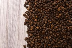 Roasted coffee beans in bulk on a light wooden background. dark cofee roasted grain flavor aroma cafe, natural coffe shop. Background, top view from above, copy stock image