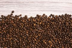 Roasted coffee beans in bulk on a light wooden background. dark cofee roasted grain flavor aroma cafe, natural coffe shop. Background, top view from above, copy royalty free stock images