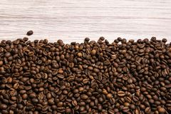 Roasted coffee beans in bulk on a light wooden background. dark cofee roasted grain flavor aroma cafe, natural coffe shop. Background, top view from above, copy royalty free stock photo