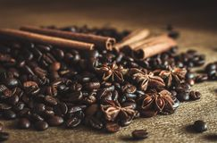 Roasted coffee beans in bulk on a table with cinnamon and star anise. . Dark still life - Image. Roasted coffee beans in bulk on a table with cinnamon and star stock photography
