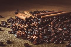 Roasted coffee beans in bulk on a table with cinnamon and star anise. . Dark still life - Image. Roasted coffee beans in bulk on a table with cinnamon and star royalty free stock images