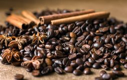 Roasted coffee beans in bulk on a table with cinnamon and star anise. . Dark still life - Image. Roasted coffee beans in bulk on a table with cinnamon and star royalty free stock photo