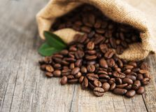 Roasted coffee beans. In burlap bag on old table Royalty Free Stock Image