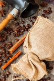Roasted coffee beans with burlap sac, Cezve, on old weathered wood, cinnamon, anis. Vintage, rustic background . Top Royalty Free Stock Photo