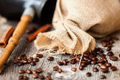 Roasted coffee beans, burlap sac, Cezve, rustic wooden table, cinnamon. Vintage background . Place for text. Top view. Roasted coffee beans, burlap sac, Cezve Stock Photography