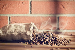 Roasted coffee beans in burlap sack Stock Images