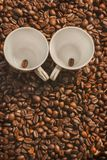 Roasted coffee beans, can be used as a background. Coffee frame of roasted beans with two cups royalty free stock photos