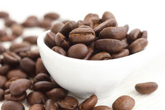 Roasted coffee beans in ceramic measuring scoop. Royalty Free Stock Images