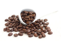 Roasted coffee beans in ceramic measuring scoop. Stock Photos