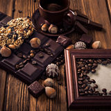 Roasted coffee beans, chocolate, candy, nuts, cup and the frame for inscriptions on the wooden background Royalty Free Stock Images